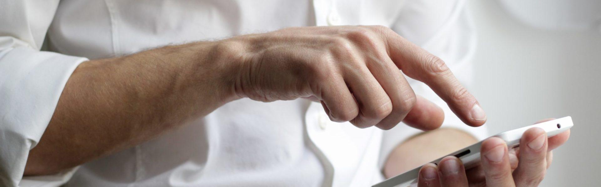 un homme en chemise blanche en train de consulter son téléphone portable